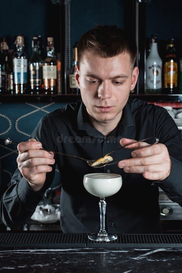 Barman faisant la garniture de cocktail de lait de poule avec des puces d'un citron photos stock