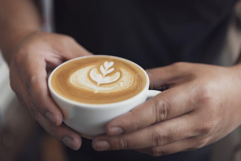Barman faisant le latte ou l'art de cappuccino avec la mousse écumeuse, tasse de café en café photos stock