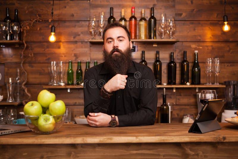Barman farpado ? moda em uma camisa no fundo do contador da barra foto de stock