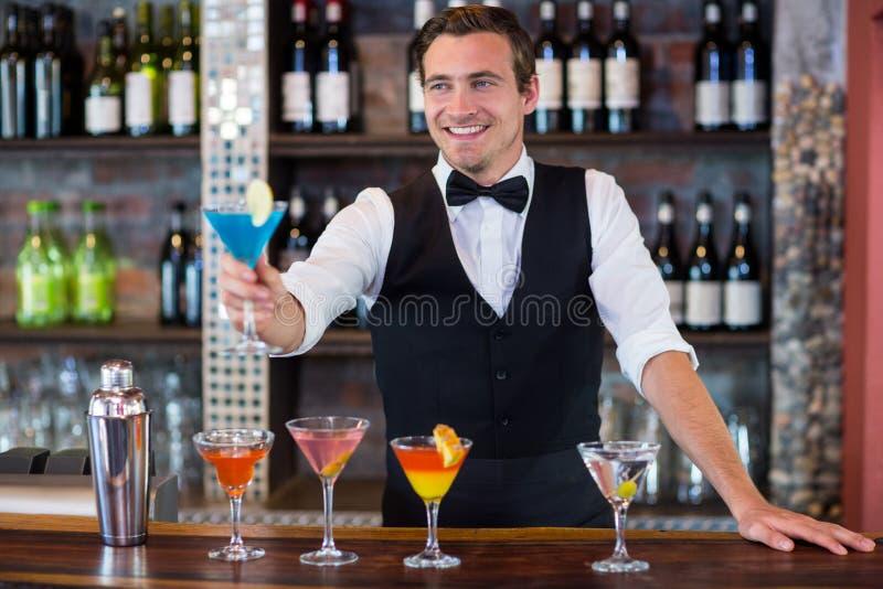 Barman feliz que serve um martini azul foto de stock