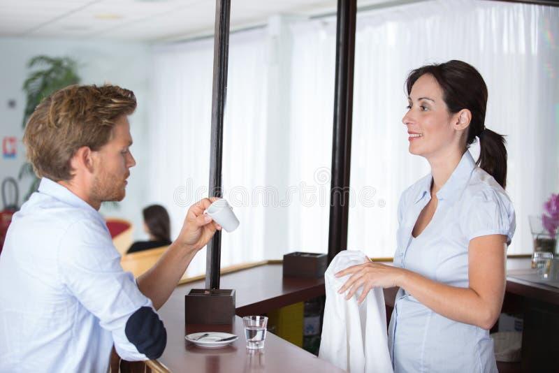 Barman femelle de sourire et client beau au compteur image libre de droits
