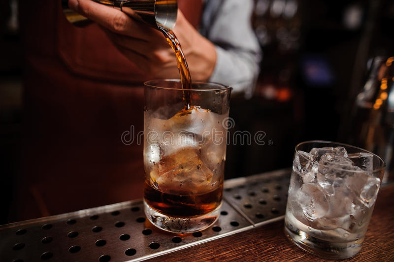 Barman hand pouring drink from measuring cup into cocktail glass filled royalty free stock photography
