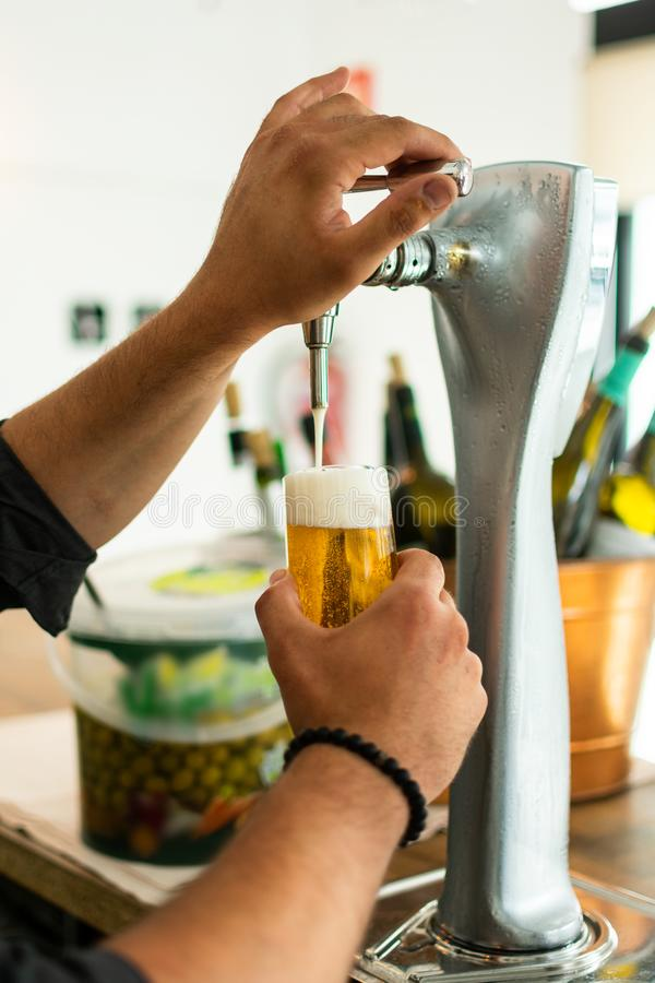 Barman hands at beer tap pouring a draught lager beer serving in a restaurant or pub. Profession, concept royalty free stock photography