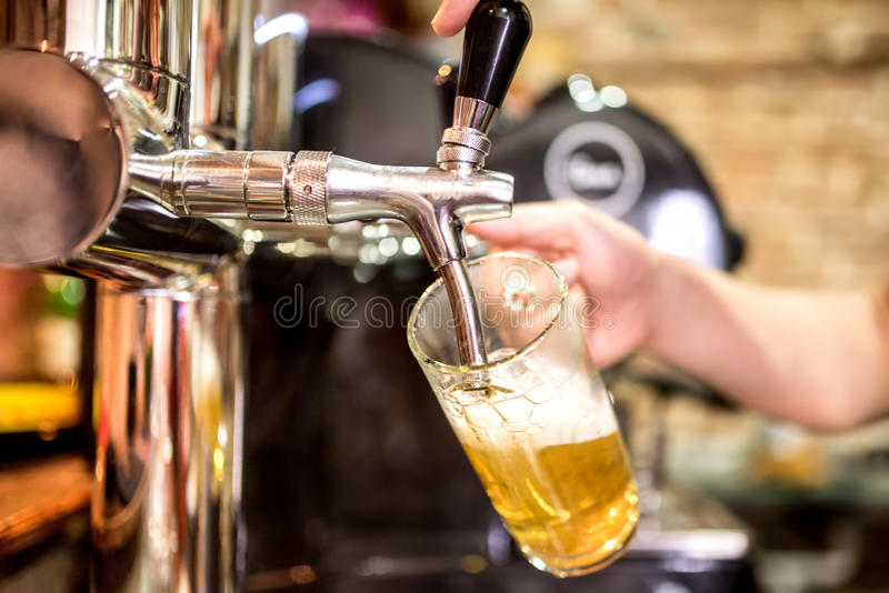 Barman hands at beer tap pouring a draught lager beer serving in a restaurant or pub. Barman hand at beer tap pouring a draught lager beer serving in a stock photos