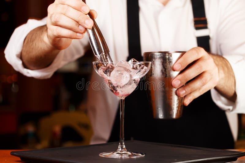 Barman in het maken van cocktail bij een nachtclub Gestemde Foto stock fotografie