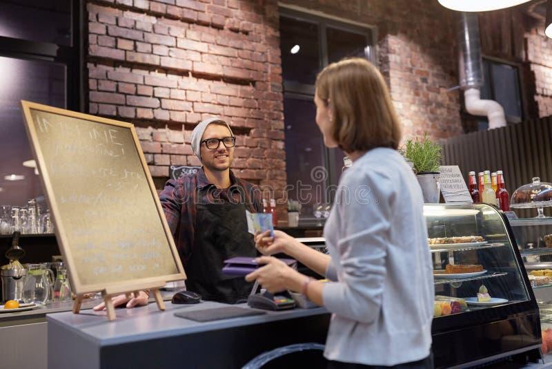 Barman heureux et femme payant l'argent au café photographie stock libre de droits