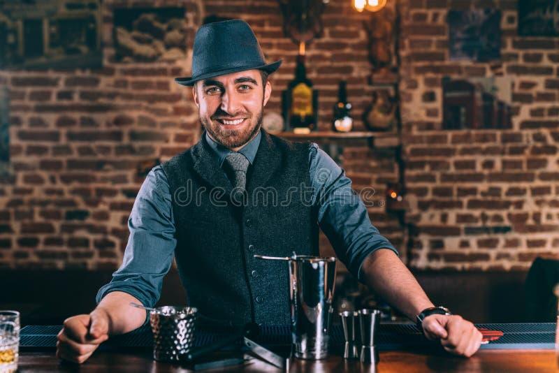 Barman heureux et souriant préparant des cocktails et appréciant le travail à la barre image libre de droits