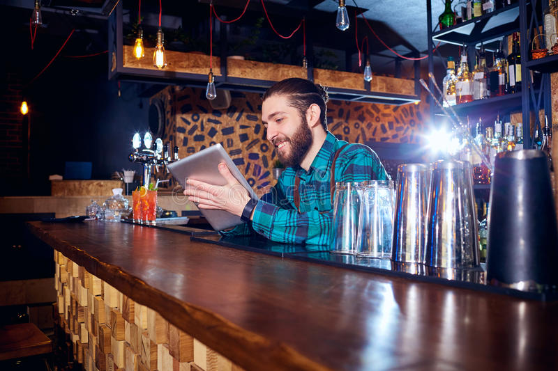 Barman with a hipster beard looks at laptop behind counter in stock photography
