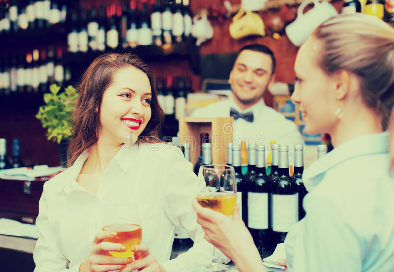 Barman i dwa dziewczyny przy barem zdjęcia stock