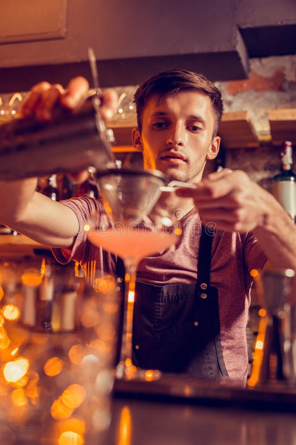 Barman jest ubranym miedza fartucha robi koktajlowi z sokiem obrazy royalty free
