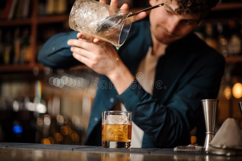 Barman kończy przygotowywać alkoholicznego koktajl Staromodnego obrazy stock
