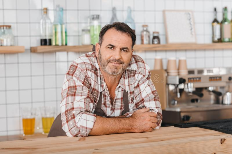 barman maduro feliz no café que inclina-se no contador e na vista da barra fotos de stock