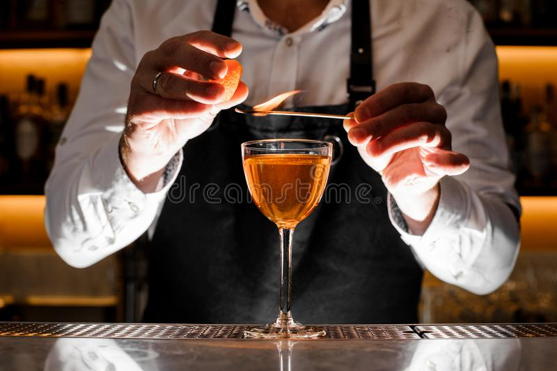 Barman making a fresh alcoholic cocktail with smoky note. Barman in white shirt making a fresh alcoholic cocktail with smoky note on the bar counter stock image