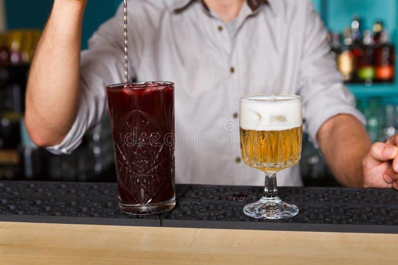 Barman& x27; manos de s en cóctel de fabricación interior de la baya del alcohol de la barra fotos de archivo