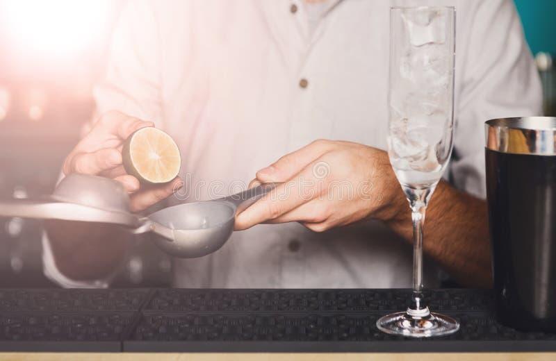 Barman& x27; manos de s que hacen el cóctel con la cal imagenes de archivo