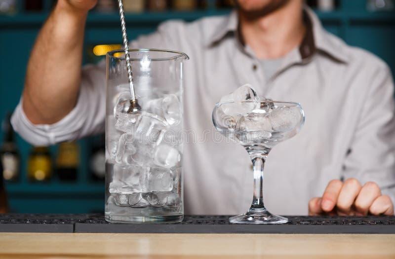 Barman& x27; manos de s que hacen el hielo para el cóctel imagen de archivo