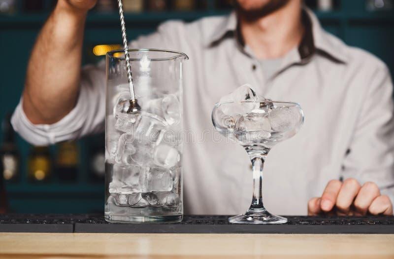 Barman& x27; manos de s que hacen el hielo para el cóctel imagenes de archivo