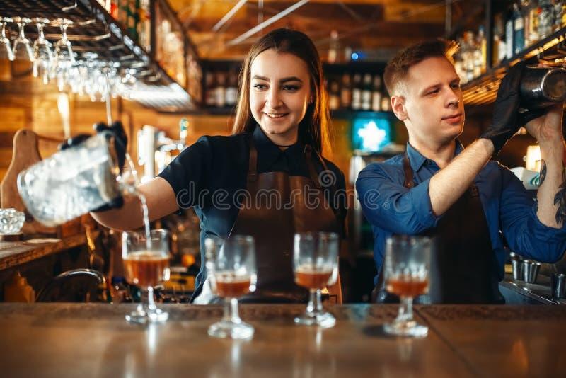 Barman masculino e fêmea no contador da barra imagem de stock royalty free