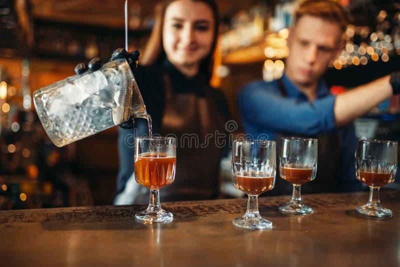 Barman masculino e fêmea no contador da barra foto de stock
