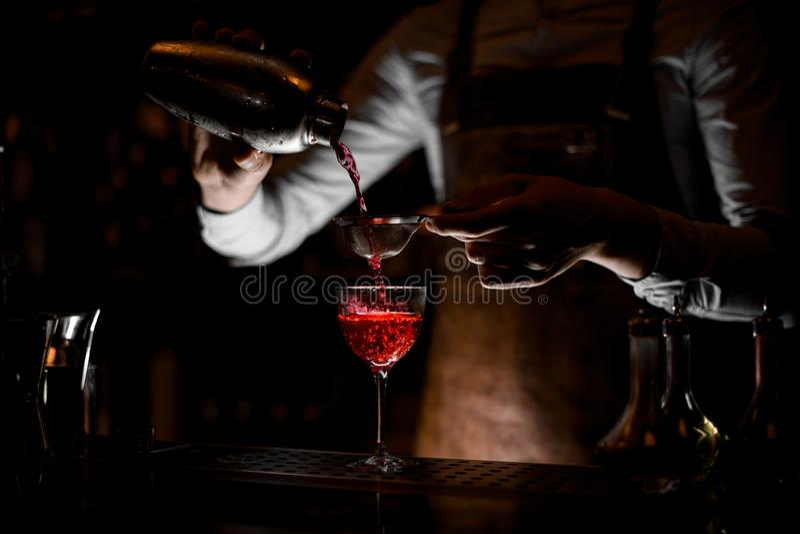 Barman masculino no avental de couro que derrama uma bebida alcoólica vermelha do abanador de aço através da peneira na obscurida imagens de stock royalty free