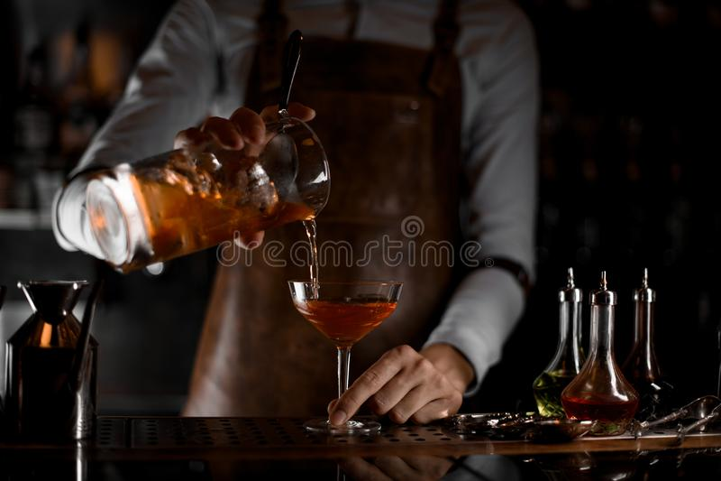 Barman masculino profissional que derrama um cocktail alcoólico marrom do copo de medição ao vidro na obscuridade imagens de stock royalty free