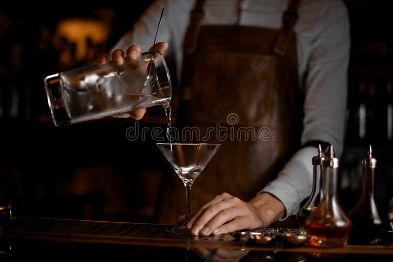 Barman masculino profissional que derrama uma bebida alcoólica do copo de medição ao vidro de martini fotos de stock