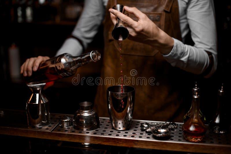 Barman masculino profissional que derrama uma bebida alcoólica do jigger de aço ao abanador de cocktail imagens de stock