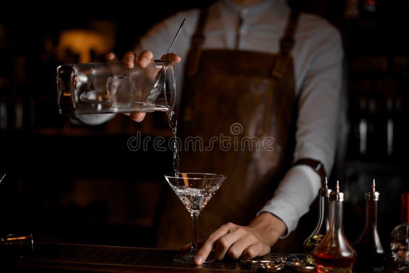 Barman masculino que derrama uma bebida alcoólica do copo de medição ao vidro de martini fotos de stock royalty free
