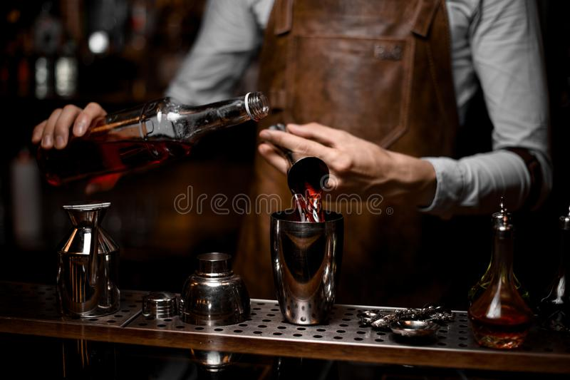 Barman masculino que derrama uma bebida alcoólica do jigger de aço ao abanador de cocktail imagens de stock royalty free