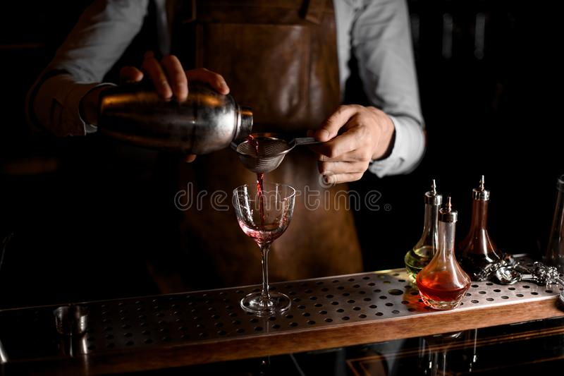 Barman masculino que derrama uma bebida alcoólica vermelha do abanador de aço através da peneira fotos de stock