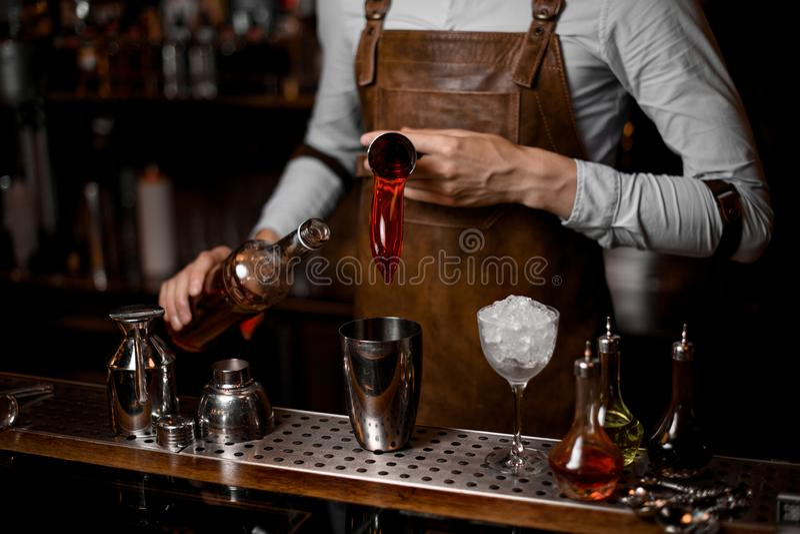 Barman masculino que derrama uma bebida alcoólica vermelha do jigger de aço ao abanador de cocktail imagens de stock