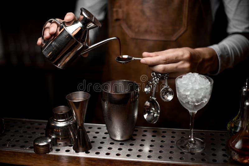Barman masculino que derrama uma essência da chaleira de aço à colher fotos de stock