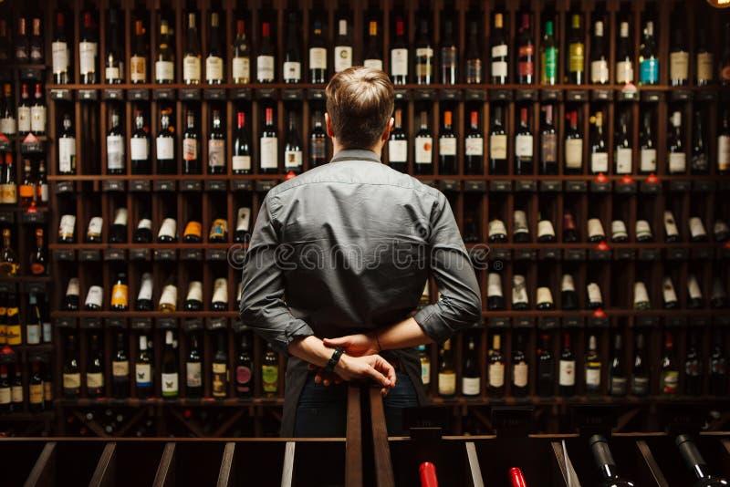 Barman na adega de vinho completamente das garrafas com bebidas excelentes fotos de stock