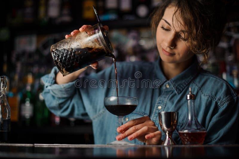 Barman nalewa brązowi alkoholicznego koktajl od pomiarowej filiżanki szkło obrazy royalty free