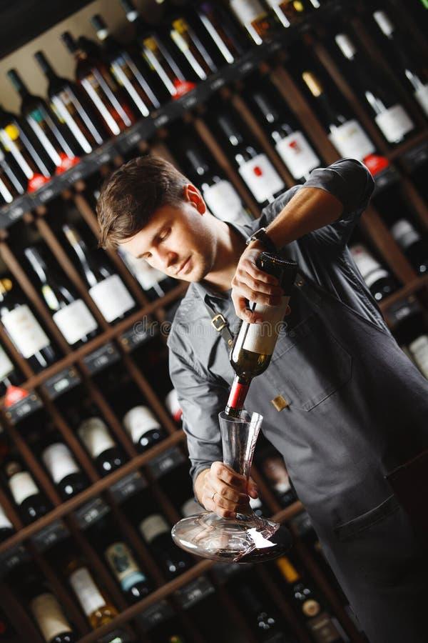 Barman nalewa czerwone wino w przejrzystym naczyniu w lochu zdjęcia stock