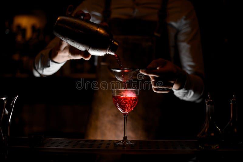 Barman no avental de couro que derrama uma bebida alcoólica vermelha do abanador de aço através da peneira na obscuridade fotos de stock