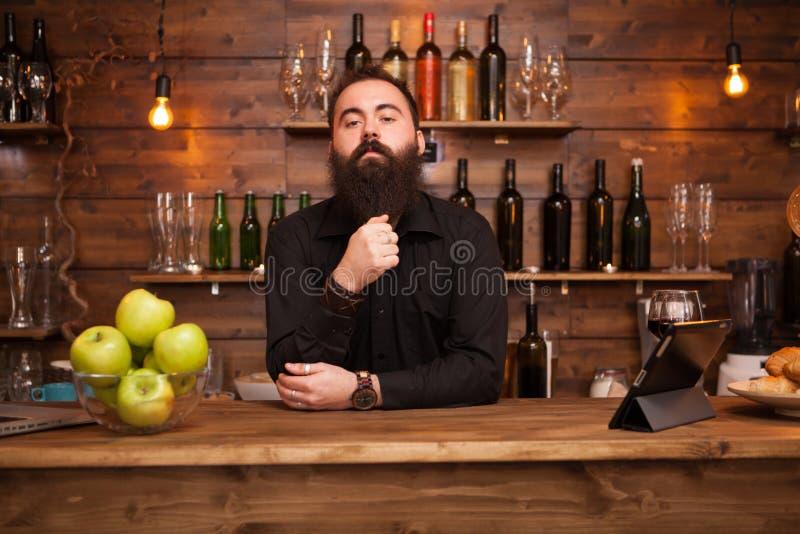 Barman novo consider?vel farpado atr?s do contador da barra imagens de stock