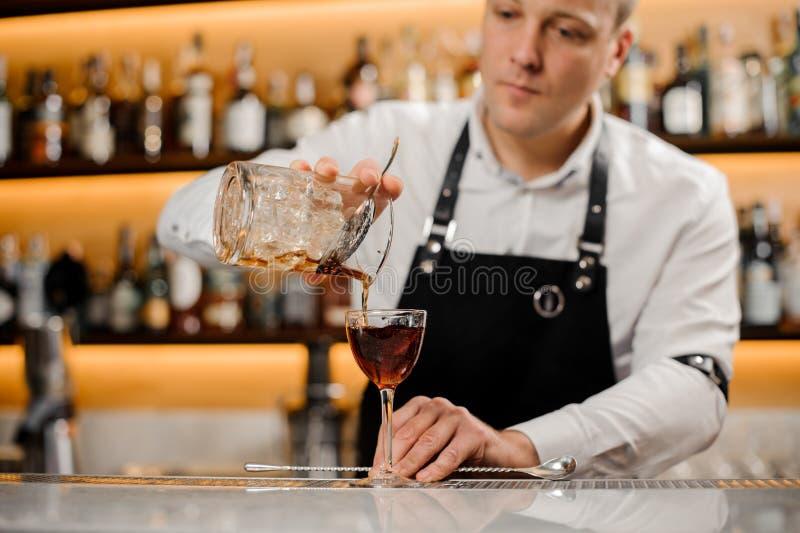 Barman novo que adiciona a bebida alcoólica em um vidro elegante fotos de stock