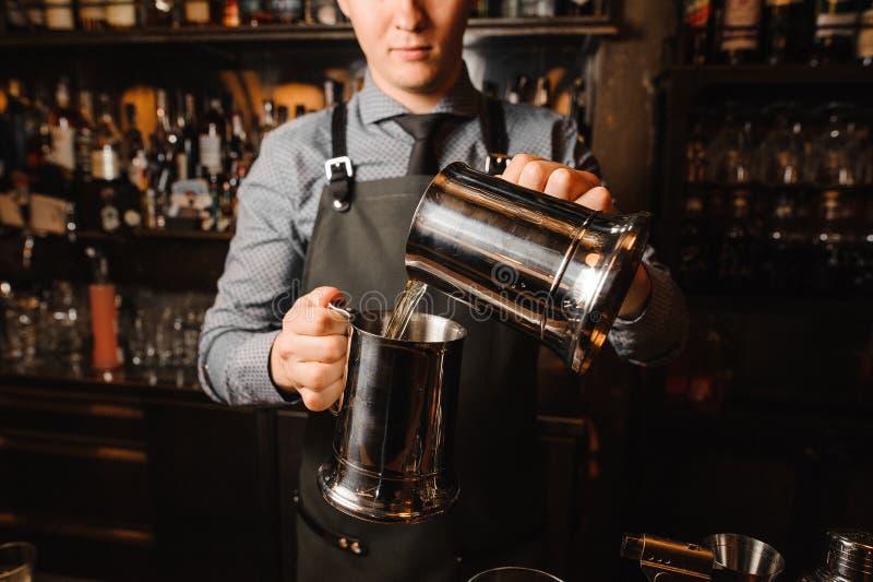 Barman novo que amua uma bebida alcoólica clara imagens de stock