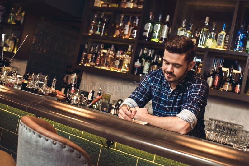 Barman novo que inclina-se na escrita do contador da barra no caderno alegre imagens de stock royalty free