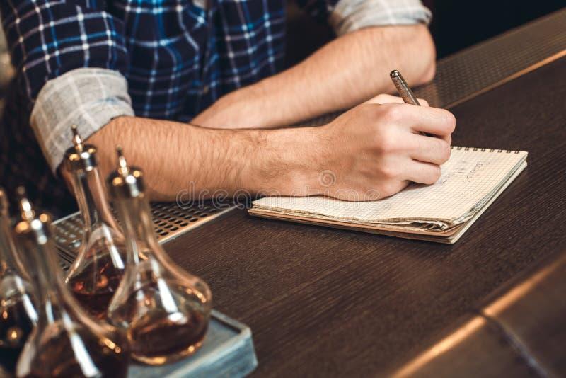 Barman novo que inclina-se no close-up do inventário da escrita do contador da barra imagens de stock royalty free