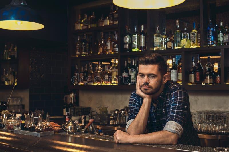 Barman novo que inclina-se no contador da barra pensativo fotografia de stock royalty free