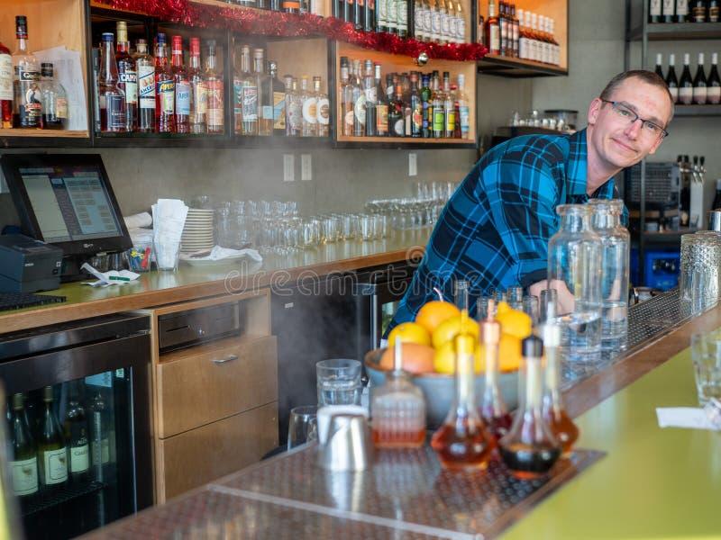 Barman otwiera zmywarkiego do naczyń za odpierającą pozwala kontrparą za zdjęcie royalty free