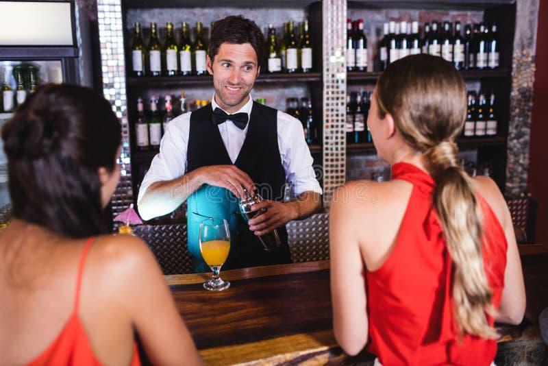 Barman parlant avec le client au compteur de barre photographie stock libre de droits