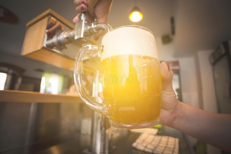 Barman pouring beer into glass in restaurant, pub, bar. Drinking beer in pub. Draft beern stock image