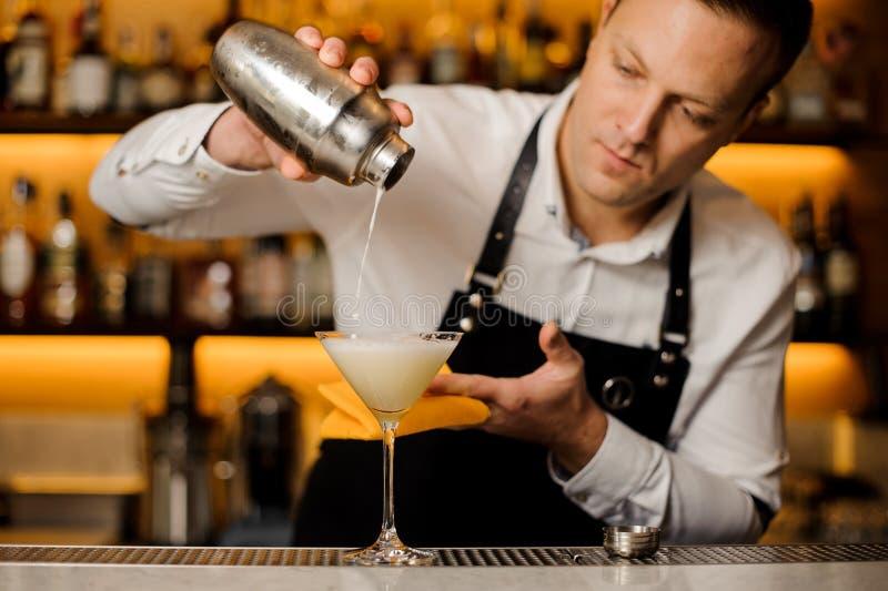 Barman pouring a fresh alcoholic drink into a cocktail glass. Barman pouring a fresh alcoholic drink into an elegant cocktail glass on the bar counter stock photos