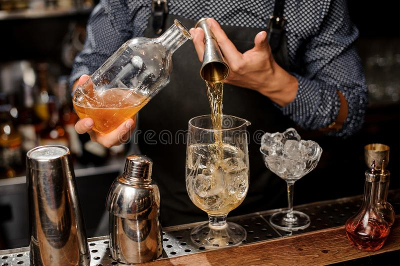 Barman pouring a portion of syrup from the bottle into the large cocktail glass. With ice cubes on the bar counter royalty free stock images