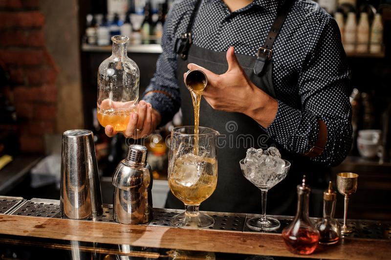 Barman pouring a portion of syrup into the large cocktail glass. With ice cubes on the bar counter stock photo
