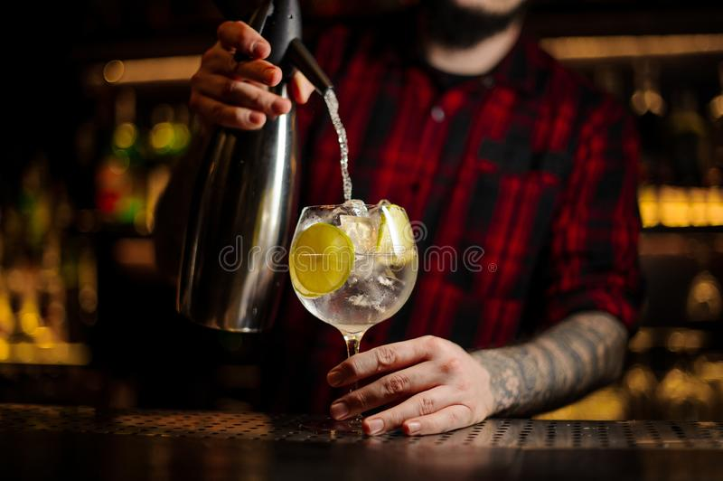 Barman pouring soda into a cocktail glass with drink and lime royalty free stock photos