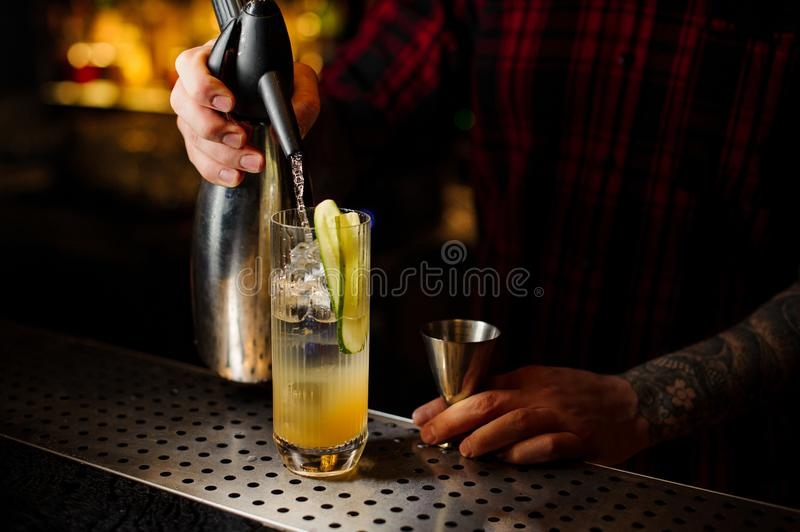 Barman pouring soda into a glass with cucumber making fresh. Sour and bitter cocktail with juice royalty free stock image